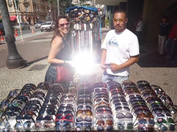 Lu experimentando óculos fashion em frente à Galeria do Rock e tentando estragar a minha foto